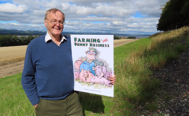 Andrew Arbuckle holding front cover of Farming is Still a Funny Business